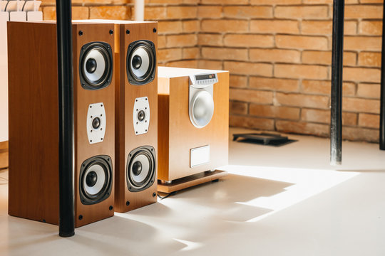 Musical stereo speakers and wooden subwoofer in the interior of a bright room. Musical concept.