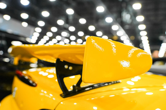 Yellow racing spoiler on the car Close-up. The concept of a sports car.