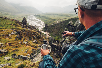 Hiking Adventure Tourism Concept. Young Traveler Man Holding Thermos In His Hand And Enjoy View Of Summer Valley, Rear View