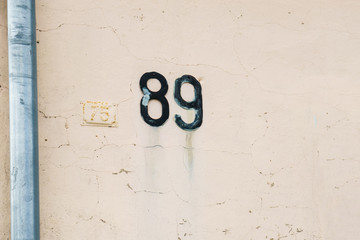 house number 89 on the wall ( eighty nine. )