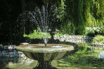 Beautiful old retro vintage park fountain with gushing sparkling jets