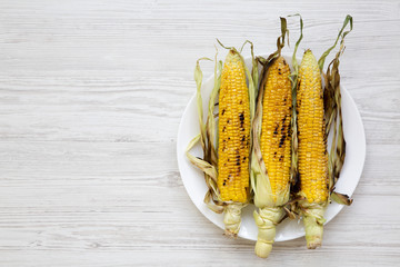 Grilled corn cobs on a round plate over white wooden surface, top view. From above, overhead, flat lay. Copy space and text area.