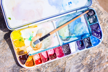 Artistic equipment: paint brushes, palette and paintings on rock in nature at sunny summer day - creation, drawing and freedom concept