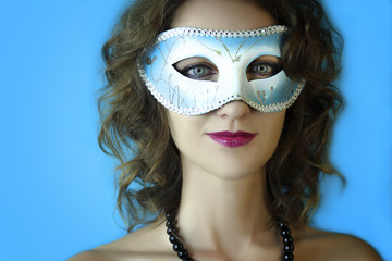 Portrait of beautiful young woman in mysterious blue carnival mask. Fashion and beauty photo