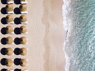 Aerial view of amazing turquoise sea with brown straw umbrellas and sun loungers. Beautiful sunny summer day in Sardinia, Mediterranean sea, Italy..
