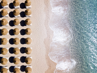Aerial view of amazing turquoise sea with brown straw umbrellas and sun loungers. Beautiful sunny summer day in Sardinia, Mediterranean sea, Italy.. Wall mural