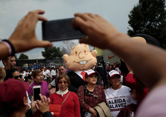 Supporters of Mexican presidential candidate Andres Manuel Lopez Obrador have their pictures taken with a person wearing an outfit resembling Lopez Obrador, while arriving at the country's largest soccer stadium for his closing campaign rally, in Mexico Ci
