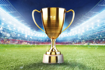 Golden winner s cup in the middle of a soccer stadium with audience
