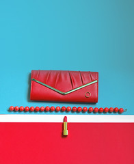 Set of fashionable women's things, red women's clutch, bag, purse, red lipstick and bijouterie, glamorous fashion photo.