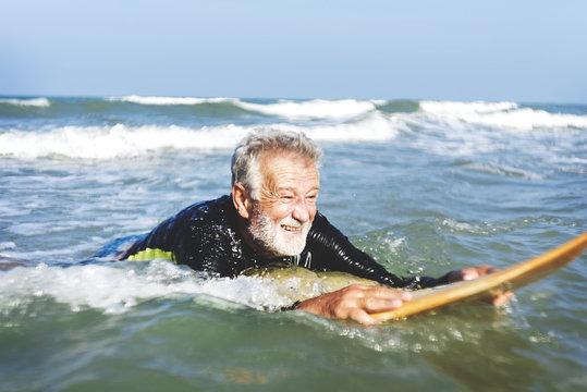 A senior man on a surfboard