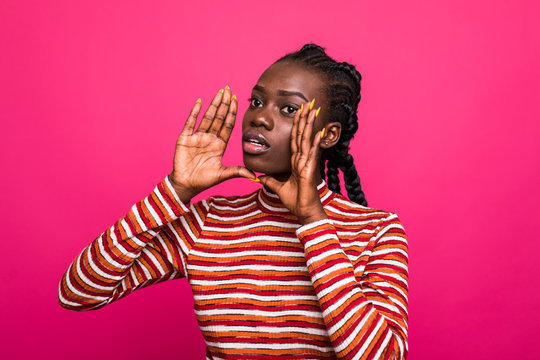Young african American woman shouting on pink background