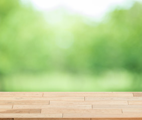 Wood table top on blur green background of trees in the park - can be used for display or montage your products.