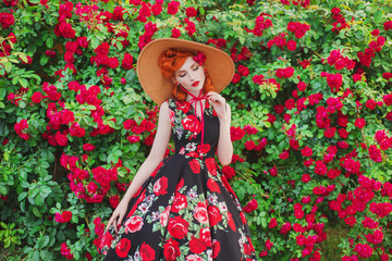 Retro girl with red lips in a dress with a print of roses on a beautiful summer background. Young redhead model in a hat on a background of a bush of roses. Stylish woman. Fashionable summer dress
