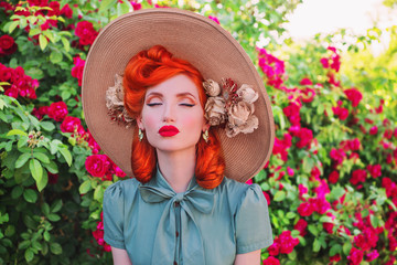 Luxury retro girl with red lips in mint dress on a beautiful flower summer background. Young redhead model in a hat with flowers on a background of a bush of roses. Stylish woman.