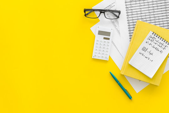 Math homework. Math textbook or tutorial near sheet with numbers, countes, calculator, notebook with formula on yellow background top view copy space
