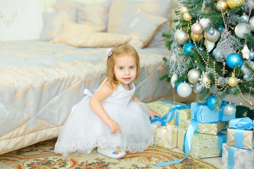 Little girl sitting near gifts under Christmas tree in bedroom. Concept of winter holidays and presents.