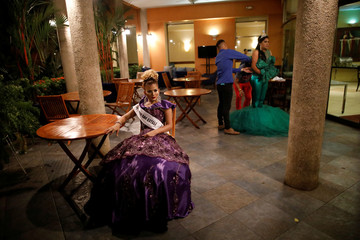 A contestant of Miss Gay Nicaragua 2018 sits as another one gets her dress ready at a hotel in Managua