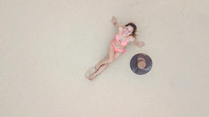 Young asian woman in a bikini lying on the beach  on the white sand near the waves, Aerial top view bikini on the beach.