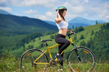 Beautiful young female rider standing with yellow bike on a grass in the mountains, wearing helmet, enjoying on summer day. Mountains, forests and blue sky on the blurred background