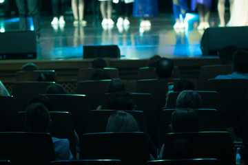 a view frombehind of the audience watching a performance on the stage