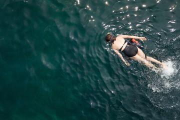 Woman swimming in blue sea. Snorkeling girl in full-face snorkeling mask. Coral reef in shallow sea. Snorkel undersea. Seashore underwater photo. Active seaside vacation. Water sport in tropical sea.