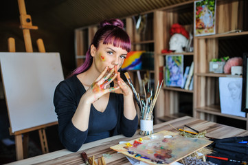 beautiful female artist with purple hair and dirty hands