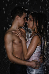 Couple young Teens together in the rain and illuminated from behind