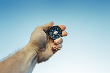 Man Scout Explorer Searching Direction With Compass On Blue Sky Background, Point Of View Shot