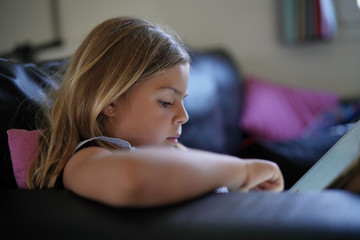 Little girl playing with digital tablet at home