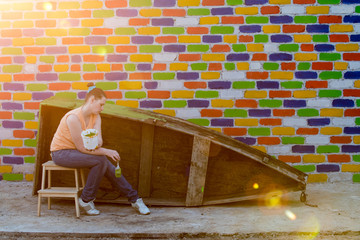 Young slender Caucasian woman paints wooden boat against brick wall background. Brush, container with paint. Romantic sunset and lighting. Preparation of background and props for photography.