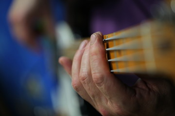 hands of a man playing an electric guitar