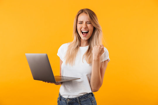Portrait of an excited young blonde girl holding laptop