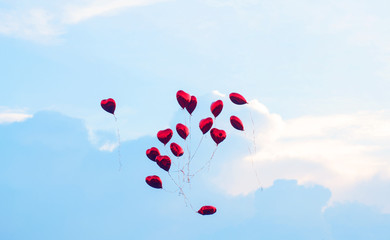 Red balls in the form of a heart fly into the blue sky.