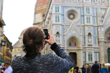 Female tourist taking phot by smartphone of Florence Cathedral in Italy. Concept of tourism and architecture of Europe.