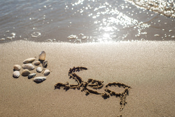 """Word """"sea"""" draw on the sand"""