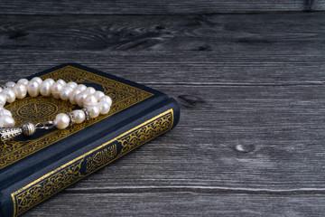 Kuala Lumpur, Malaysia- December 4, 2017: Closeup of Holy Quran/Koran with beads or Tasbih/Rosary over wooden background.Selective focus and crop fragment.