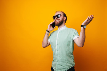 Photo of handsome excited man expressing surprise on face and gesturing while speaking on telephone over yellow background