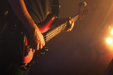 Guitarist plays on of bass guitar