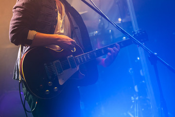 Guitarist on stage plays on electric guitar