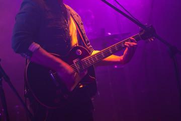 Guitarist plays on guitar in purple lights