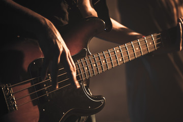Guitarist plays on of bass guitar, close up