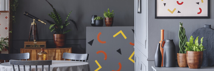 Dark grey room interior with dining table with chairs and cupboard with plants and decor in the photo with telescope and confetti patterned stickers on the wall in blurred background
