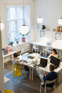 High angle view of colleagues using technologies at desk in creative office
