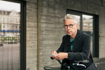 Portrait of senior man using smart phone while standing with bicycle in city