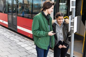 Smiling multi-ethnic teenagers standing on sidewalk against bus in city