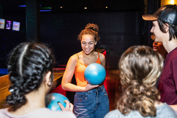Smiling teenage girl holding bowling ball while standing amidst friends