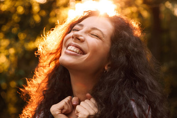 Portrait closeup of happy curly woman 18-20 lsmiling with closed eyes and expressing delight, while walking through park in sunny day with trees background