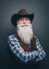 Portrait of happy senior man wearing cowboy hat against gray background