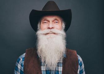 Portrait of happy bearded senior man wearing cowboy hat on gray background