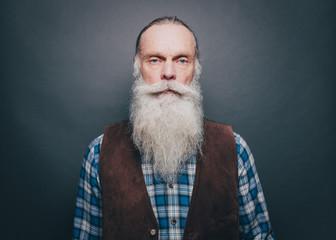Portrait of confident senior man with long white beard against gray background